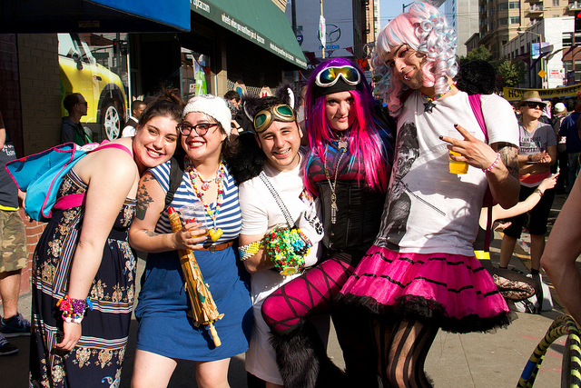 A man in a pink skirt and his friends hang out at How Weird Street Fair 2012