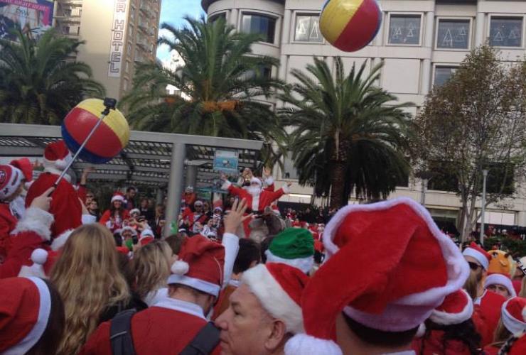 People in Santa suits celebrate SantaCon 2014 in Union Square in San Francisco.