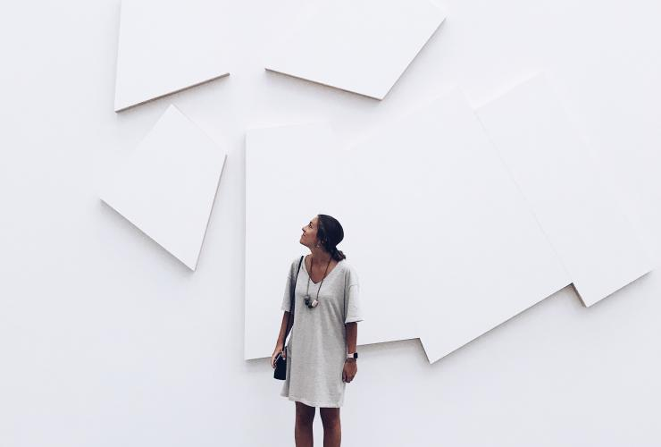 woman in front of white museum wall