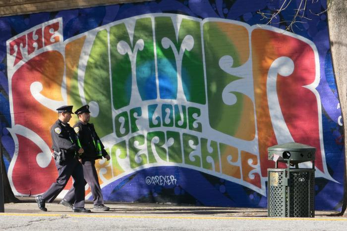 "Picture of the text ""Summer of Love"" in rainbow letters with two police officers walking by on the sidewalk."